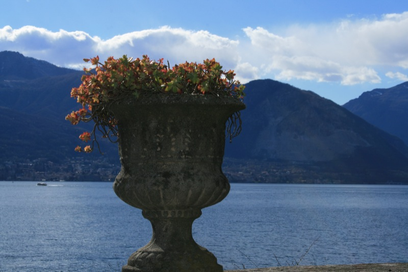The setting is magical a lakeside walk decorated with stone flower pots